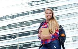 Glimlachende vrouwelijke student die zich buiten met zak en boek bevinden Stock Fotografie