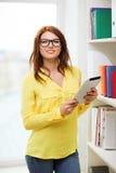 Glimlachende vrouwelijke student met tabletpc in bibliotheek royalty-vrije stock fotografie