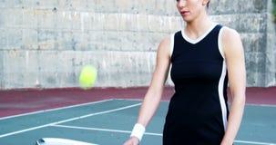 Glimlachende vrouwelijke tennisspeler met racket in het hof stock videobeelden