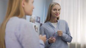 Glimlachende vrouwelijke tiener die op lipgloss zetten en in de spiegel, schoonheid kijken stock video