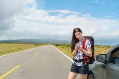 Glimlachende vrouwelijke toerist die zich naast reisauto bevinden royalty-vrije stock afbeeldingen