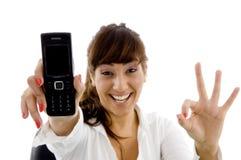Glimlachende vrouwelijke uitvoerende mobiele holding Stock Afbeeldingen