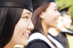 glimlachende vrouwelijke universitaire gediplomeerde met klasgenoten stock afbeelding