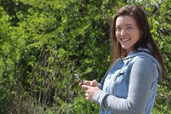 Glimlachende Vrouwelijke Universiteit/Universitaire Student Outdoors, de Telefoon Mobiele Telefoon van de Holdingscel Royalty-vrije Stock Foto's