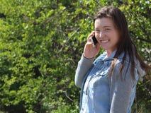 Glimlachende Vrouwelijke Universiteit/Universitaire Student Outdoors, die de Mobiele Telefoon van de Celtelefoon met behulp van Stock Foto