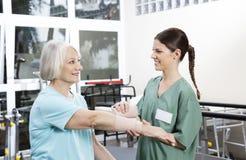 Glimlachende Vrouwelijke Verpleegster Putting Crepe Bandage op Han van de Hogere Vrouw Stock Foto's