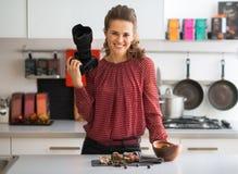 Glimlachende vrouwelijke voedselfotograaf in keuken Stock Foto