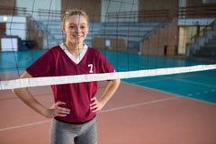 Glimlachende vrouwelijke volleyballspeler die zich met hand op heupen in het hof bevinden royalty-vrije stock foto's