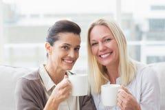Glimlachende vrouwelijke vrienden die koffie in woonkamer hebben Stock Fotografie