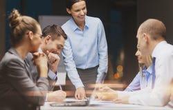 Glimlachende vrouwelijke werkgever die aan commercieel team spreken stock foto