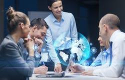 Glimlachende vrouwelijke werkgever die aan commercieel team spreken Stock Fotografie