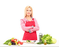 Glimlachende vrouwelijke werknemer die met schort salade voorbereiden Stock Fotografie