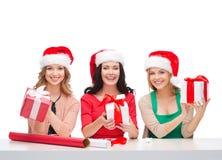 Glimlachende vrouwen in de hoeden van de santahelper met giftdozen Stock Foto
