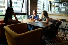Glimlachende vrouwen die bij restaurant zitten en met koppen van koffie spreken Royalty-vrije Stock Foto's
