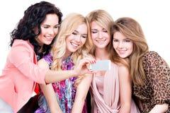 Glimlachende vrouwen die de mobiele telefoon bekijken stock afbeeldingen