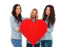3 glimlachende vrouwen die hun groot rood hart aanbieden aan u Stock Afbeelding