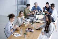 Glimlachende vrouwen die lunch eten stock afbeeldingen