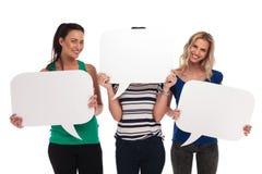 3 glimlachende vrouwen die toespraakbellen, één houden die haar gezicht behandelen Stock Foto