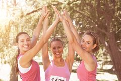 Glimlachende vrouwen die voor de voorlichting van borstkanker lopen stock afbeeldingen