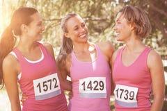 Glimlachende vrouwen die voor de voorlichting van borstkanker lopen stock foto's