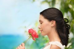 Glimlachende vrouwen ruikende bloem Stock Foto's