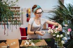 Glimlachende vrouwenbloemist die boeket in bloemwinkel maken royalty-vrije stock fotografie