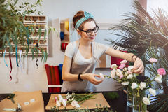 Glimlachende vrouwenbloemist die boeket in bloemwinkel maken stock fotografie