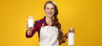 Glimlachende vrouwenkok die glas eigengemaakte verse rauwe melk geven royalty-vrije stock afbeelding