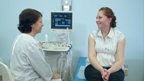 Glimlachende vrouwenpatiënt die overleg met vrouwelijke arts hebben Royalty-vrije Stock Foto