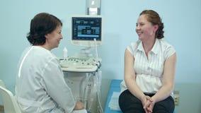Glimlachende vrouwenpatiënt die overleg met vrouwelijke arts hebben stock video