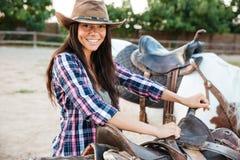 Glimlachende vrouwenveedrijfster die en zadel voor het berijden van paard bevinden zich voorbereiden royalty-vrije stock foto's