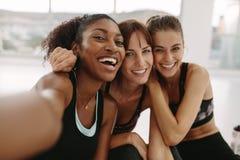 Glimlachende vrouwenvrienden die selfie in geschiktheidsstudio nemen royalty-vrije stock afbeelding