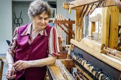 Glimlachende vrouwenwever die aan weefgetouw de sjaalkleding van productiewhool werken Royalty-vrije Stock Afbeelding
