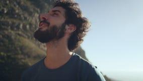 Glimlachende wandelaar die bergen bekijkt stock videobeelden