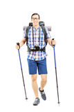 Glimlachende wandelaar met rugzak en wandelingspolen het lopen Stock Foto's