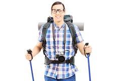 Glimlachende wandelaar met rugzak en wandelingspolen het lopen Royalty-vrije Stock Foto