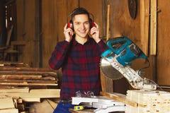 Glimlachende werkman in het geruite overhemd en het dragen van beschermende hoofdtelefoons die met cirkelzaag bij de zaagmolen we stock foto