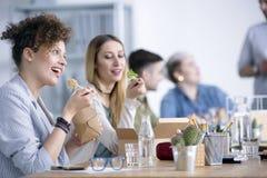 Glimlachende werknemers die lunch eten stock afbeelding