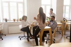 Glimlachende werknemers die van pizza genieten die middagpauze binnen hebben gedeeld van royalty-vrije stock foto's