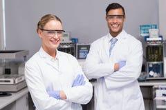 Glimlachende wetenschappers die gekruiste camerawapens bekijken Stock Foto's