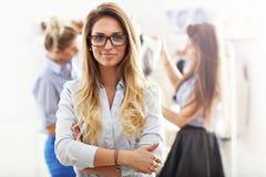 Glimlachende winkelmanager voor haar boutique stock fotografie