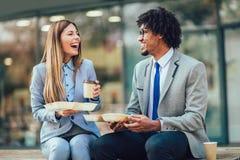 Glimlachende zakenlieden die met sandwiches voor het bureaugebouw zitten - middagpauze royalty-vrije stock fotografie