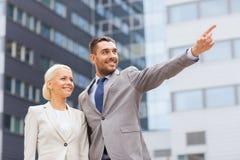 Glimlachende zakenlieden die zich over de bureaubouw bevinden Stock Afbeeldingen