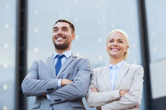 Glimlachende zakenlieden die zich over de bureaubouw bevinden Stock Fotografie