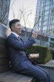Glimlachende zakenman bij lunch het texting op zijn mobiele telefoon in openlucht Stock Foto's