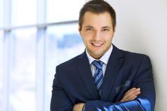 Glimlachende zakenman in bureau Stock Afbeeldingen