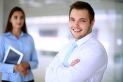 Glimlachende zakenman in bureau met collega's op de achtergrond stock foto's