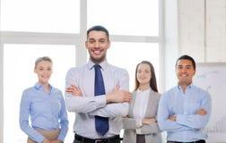 Glimlachende zakenman in bureau met team op rug Stock Foto's
