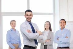 Glimlachende zakenman in bureau met team op rug Royalty-vrije Stock Fotografie
