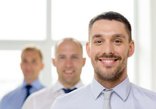 Glimlachende zakenman in bureau met team op rug Stock Afbeelding